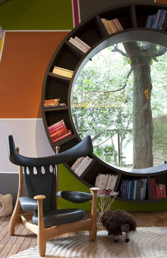 Round Window Bookcase - What better place for a reading corner, than next to a beautiful window, with garden views? In todayas find, this place of refugee also comes with a nice bonus: a round bookcase. Designed by Fabio Galeazzo, as part of a colorful aUrban Cabina in Sao Paoplo, Brazil, the project is unconventional and adds a great aesthetic effect. In the photos below, the contrast between the black round bookcase and the surrounding colors contributes to a playful, happy atmosphere.