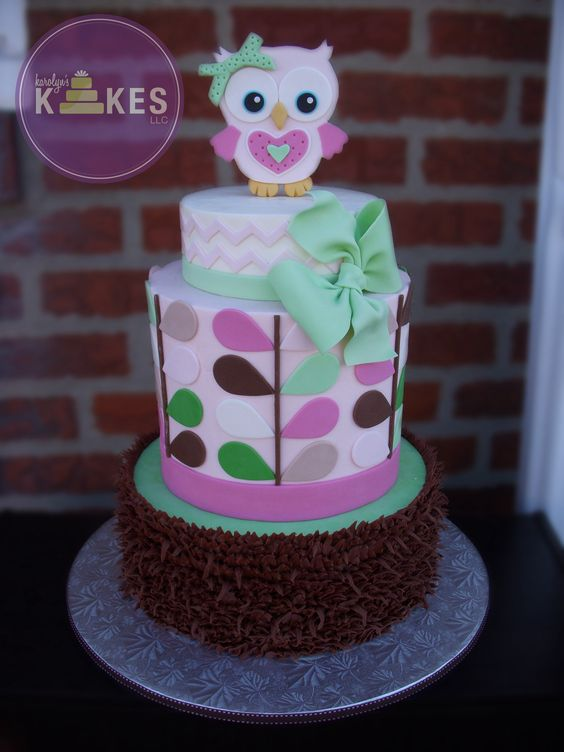 Owl baby Shower cake. All 3 tiers iced in buttercream. Chocolate buttercream feathers on bottom. Fondant leaves, chevron, bow, and owl topper.
