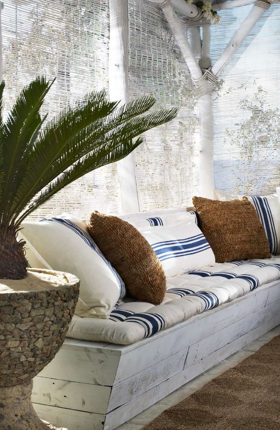 Ralph Lauren Home creates a shady beach retreat with bench cushions and throw pillows sewn from classic blue and white striped textiles.: