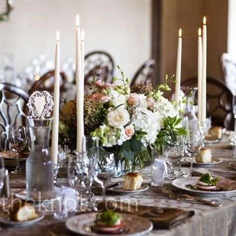 Floral and Candle Centerpieces    Tapered candles surrounded silver bowls filled with hydrangeas, delphinium, garden roses and lilies for a romantic atmosphere.  From the album: A Vineyard Wedding in Peconic, NY