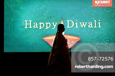"A silhouette of a woman walking in front of an electronic billboard wishing a happy Diwali to passerby's in Mumbai, India. Diwali is a major Hindu holiday and is known as the ""Festival of Lights"".  The five day festival occurs during October and/or Novemb"