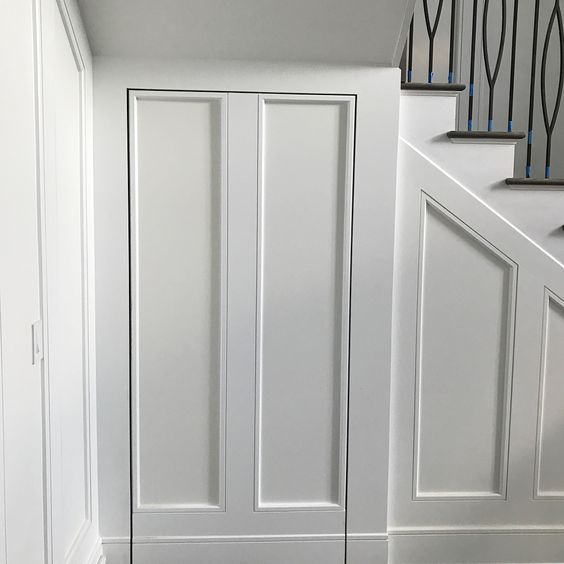 Custom millwork in the foyer... The concealed door leading to the office & lounge just needs a shoe molding and it'll be all set. Using Rixon hinges and some creative trimming can help disguise your doors in the entryway. @planarchitecture @this_flipping_family #interiordesign #grey #white #nj #new #home #trim #newjersey #design #interior #metal #rail