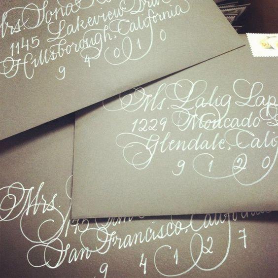 White calligraphy by Calligraphy Katrina on gold envelopes.