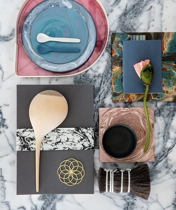 A marble table with beautiful design on top. Ceramics, woodwork and flowers.