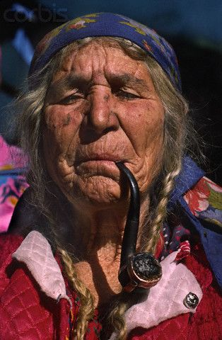 Elderly Gypsy Woman Smoking a Pipe [by Barry Lewis, Romania, 1988].