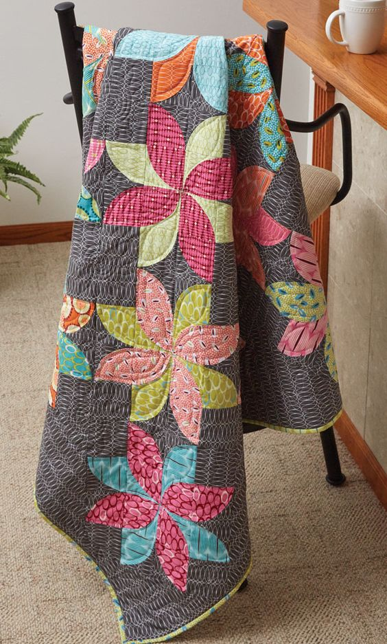 "Using 3"" curved seam units, designer Emily Bailey arranged them to create a modern floral design for this intermediate level quilt project.:"