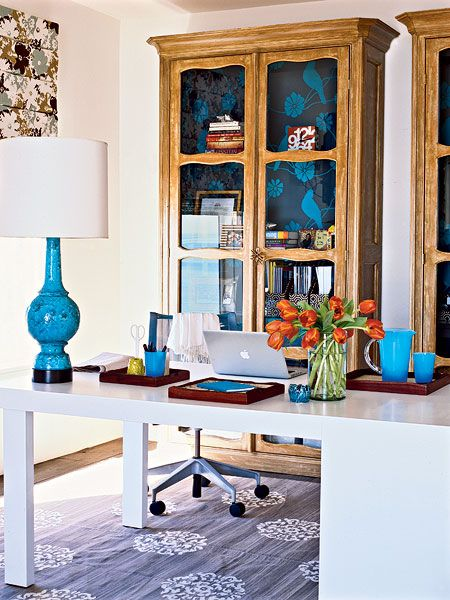 A pair of glass-front French bookcases is lined with cheerful wallpaper for pretty, functional storage space. The clean lines of a Parsons-style desk topped with organizing trays lend a tidy vibe, while turquoise desk accessories infuse the workspace with energy and excitement. (Photo: Lisa Romerein)