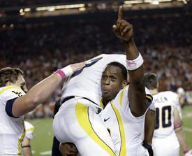 West Virginia running back Andrew Buie, top, is lifted up by quarterback Geno Smith after scoring a touchdown against Texas on Saturday in Austin.