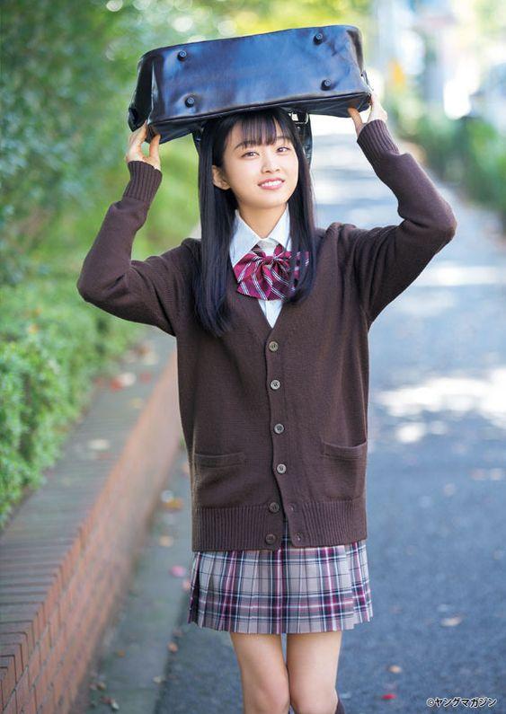 茶色のカーディガンを着た制服姿のバッグを頭の上で持つ原田葵の画像