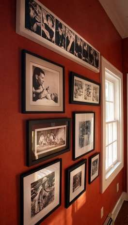 Black and white photo gallery pops on the rusty red wall.