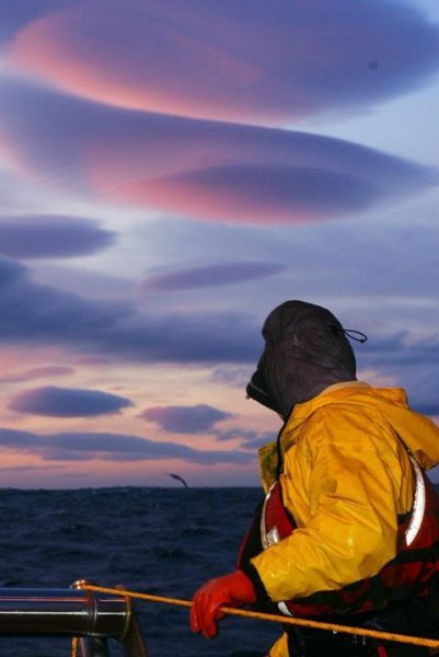 A fisherman in the Bering Sea peers up at rose and violet clouds.
