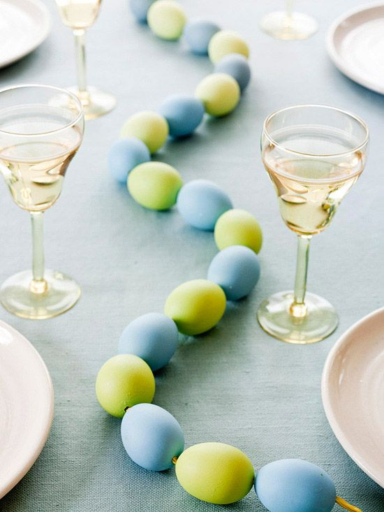Easter Egg Table Garland        Create this pretty blue-and-green Easter egg garland by stringing together about three dozen dyed blown-out eggs. To blow out an egg, use a pushpin to put a hole in each end. Gently push a wooden skewer through one end to enlarge the hole and break the yolk. Blow into the smaller hole to push out all the yolk and white. Use a bead-making needle threaded with a narrow ribbon to connect the eggs to display on your dining table for Easter.: