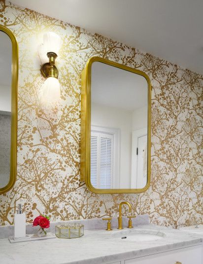 Splatter paint-inspired wallpaper adds style without stuffiness to the master bath. Matching gold accents with the mirrors, drawer handles, and sink fixtures completes the look.   - HouseBeautiful.com