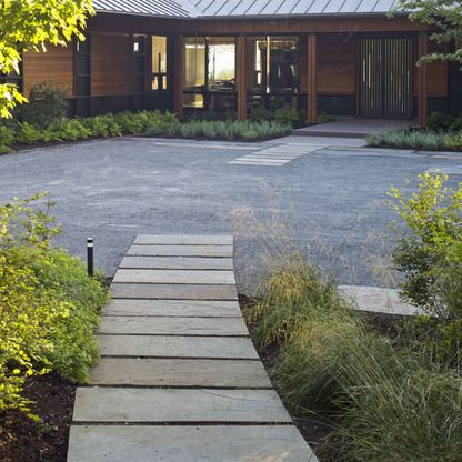 Wide cut stone pavers move through the garden into a blue gravel area, end and then restart as it nears the entry.