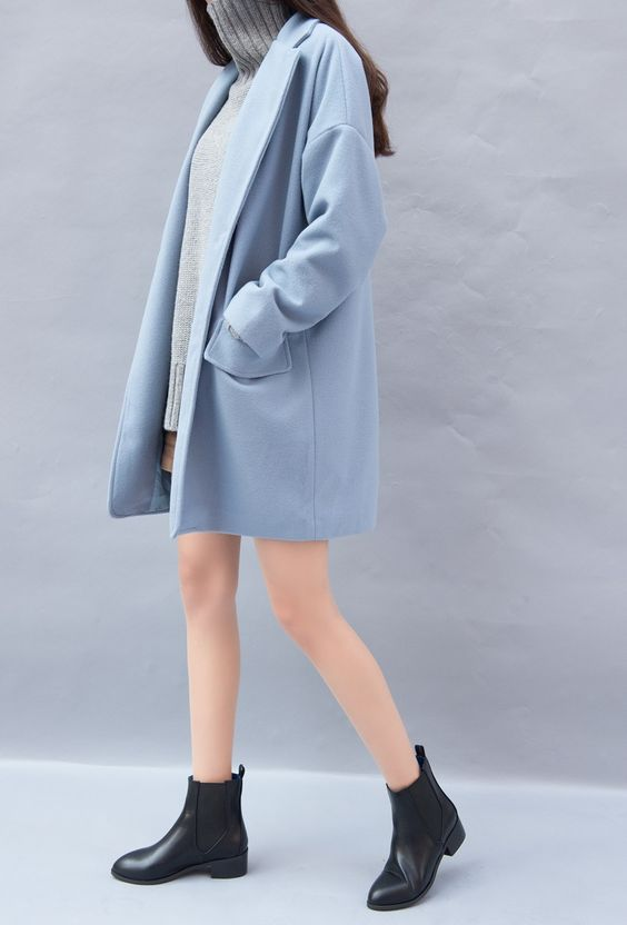 Baby blue coat over a knit gray mockneck dress