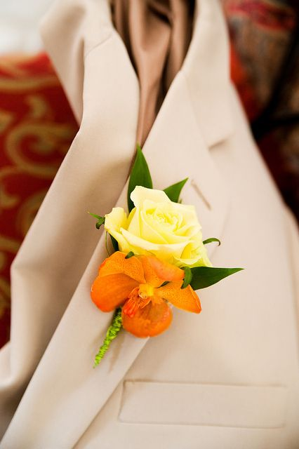 Butter yellow rose and orange orchid boutonniere. With another flower or two, this would be a lovely corsage, too.