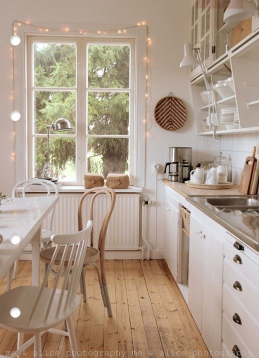 Love the atmosphere of this white kitchen + natural woorden floor + lights + open shelves + mismatched chairs.: