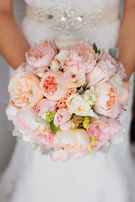 A blush bridal bouquet with peonies and white ranunculus flowers.: