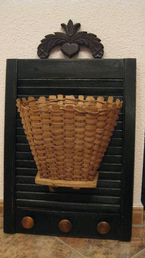 Made with an old shutter, painted black.  Flea market find topper, old dresser knobs and child's grape picking basket.