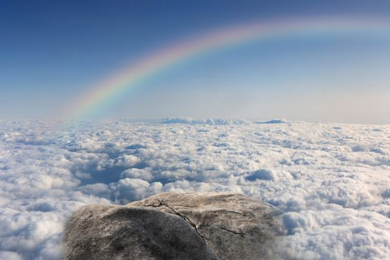Harmony of mountaintop and rainbow on white clouds