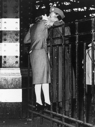 London, 1940 - A soldier kisses his sweetheart over the gates of a London railway station as he heads off to join the British Expeditionary Forces in France.