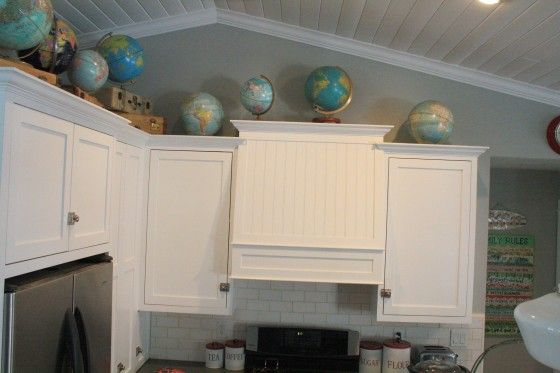 LOVE the globes and suitcases on top of the cabinets...why do they put that weird space up there?