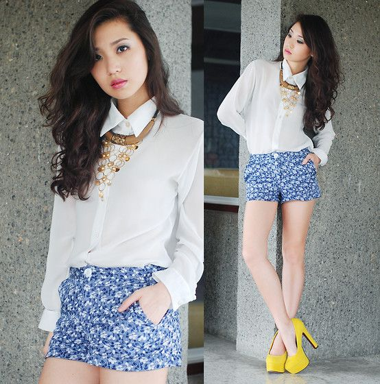 white blouse, gold necklace, blue patterned shorts, bright yellow heels