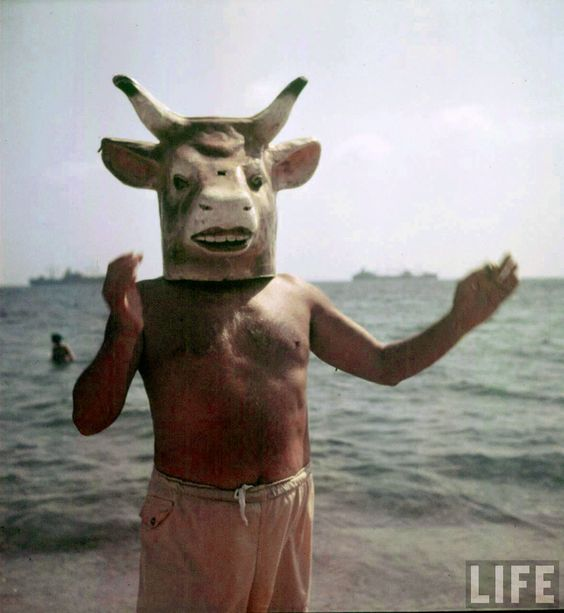 Pablo Picasso wearing a cow's head mask on beach, 1949