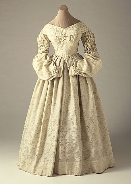 Wedding dress, (circa 1837-8).   LA County Museum of Art.  Wool brocaded with silk, Broad, 'portrait' neckline.  The upper arm of the sleeve is ruched, opening to full puffs on the forearm.  The ruching is repeated at the wrist above the cuff.