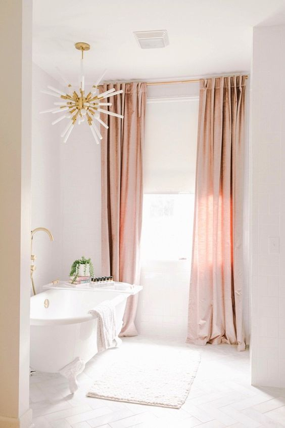 Beautiful bathroom ideas and inspiration - glam pink and cream bathroom with gold light fixture and clawfoot tub #bathroomdecor