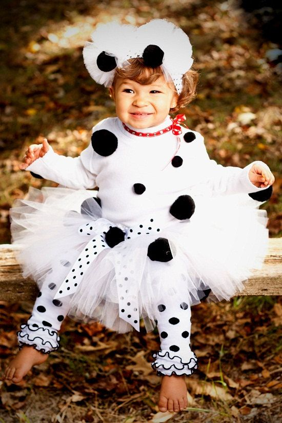 Adorable Dalmatian tutu set Halloween Costume. Tutu is made in all white and has black pom balls embellished on it. The top is a white turtle neck with a red jeweled collar that ties in a bow on the side. Black pom balls are embellished to the shirt as well. The ears are attached to a white crochet headband and are made of tulle puffs. Would be fairly easy to DIY.