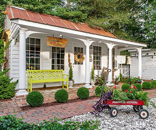 This large shed looks like anything but a storage unit. Its copper roof, welcoming porch, and colorful bench make it a true extension of the home.