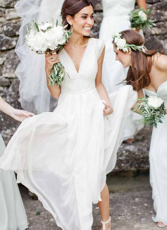 White a line chiffon beach wedding dress, pleat deep v neck on the bodice. A line skirt feature wide straps and flowing pleated hem.
