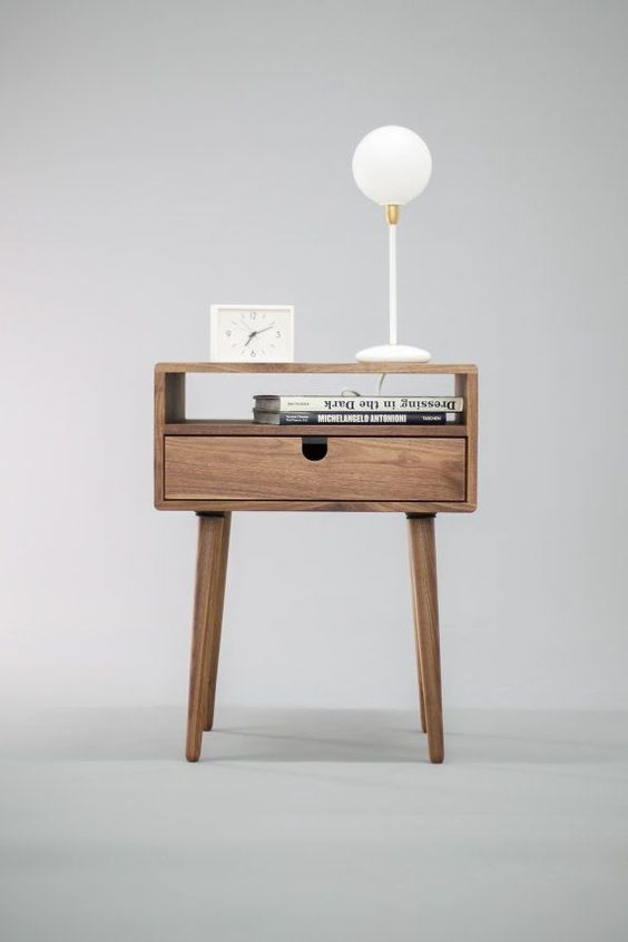 The classic design of our walnut nightstand reflects mid century modern with its clean lines and tapered legs. Its double-tier design has an open