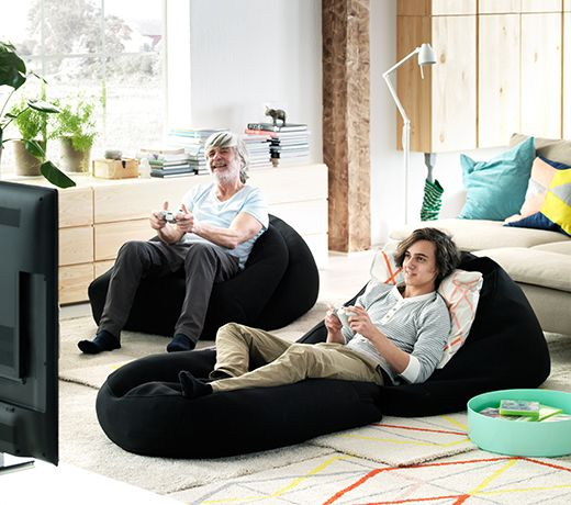Grandfather and grandson sitting on IKEA beanbags playing a video game together.