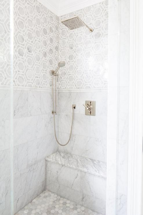 Exquisite shower features marble hex tiles on upper walls and stacked marble tiles on lower walls