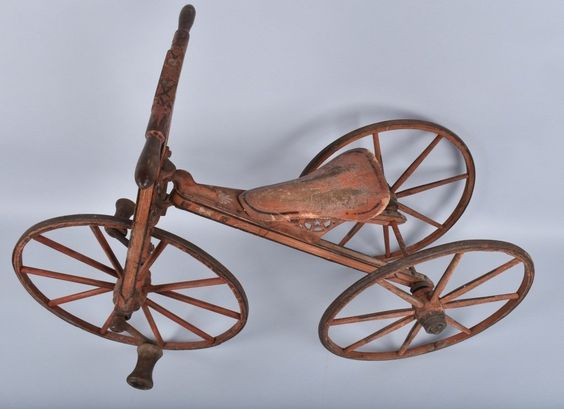"C-1870 wood trike with cast iron hardware and iron wheel bands retains 95% original salmon paint. 29"" tall and 40"" long tricycle also retains black trim paint and pinstripe. Has unusual fully carved seat."