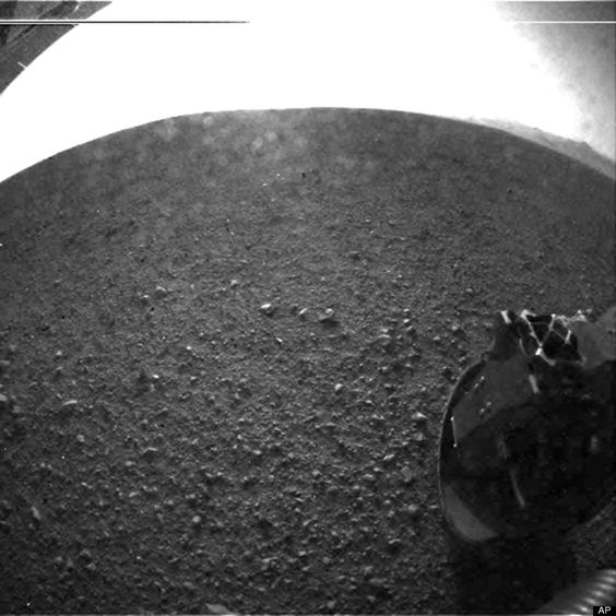 "This is one of the first images taken by NASA's Curiosity rover, which landed on Mars the evening of Aug. 5 PDT (morning of Aug. 6 EDT). It was taken through a ""fisheye"" wide-angle lens on the left ""eye"" of a stereo pair of Hazard-Avoidance cameras on the left-rear side of the rover"