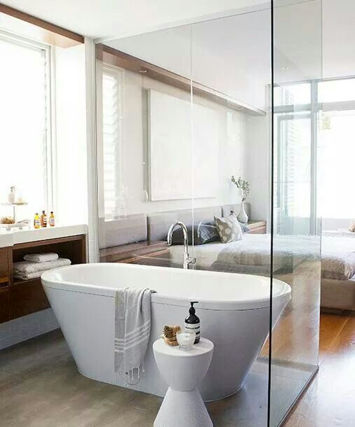 A Free Standing Bathtub Spearated With A Glass Space Divider For
