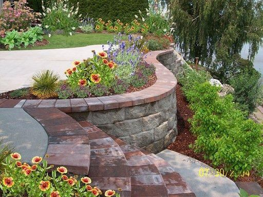 Retaining wall with patio outside backyard design for Curved garden wall ideas