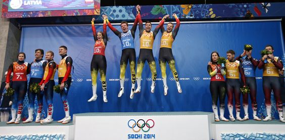 Germany's Natalie Geisenberger (5thL), Felix Loch (6thL),Tobias Arlt (6th R) and Tobias Wendt (5th R) leap on the podium celebrating their f...