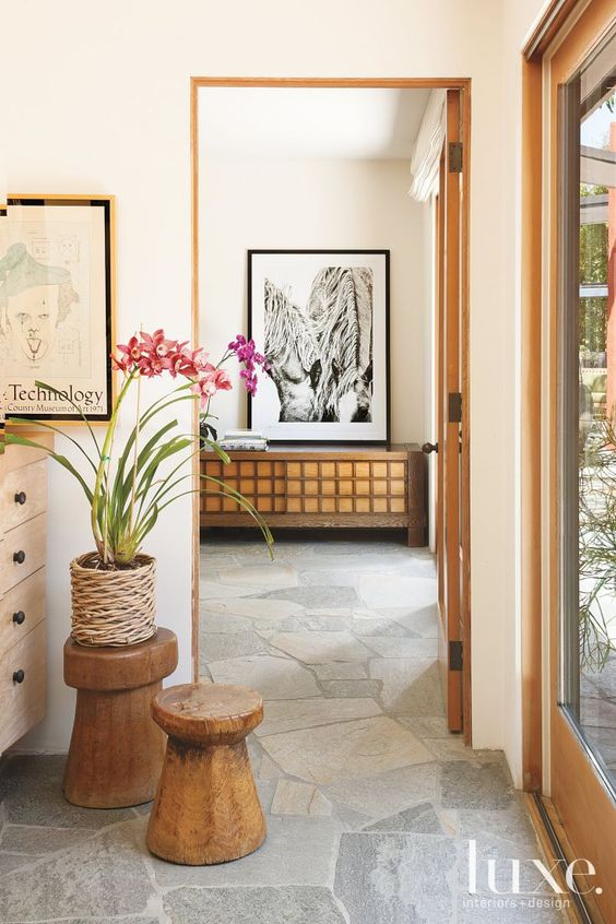 Stone foyer, natural wood stools and potted orchids..