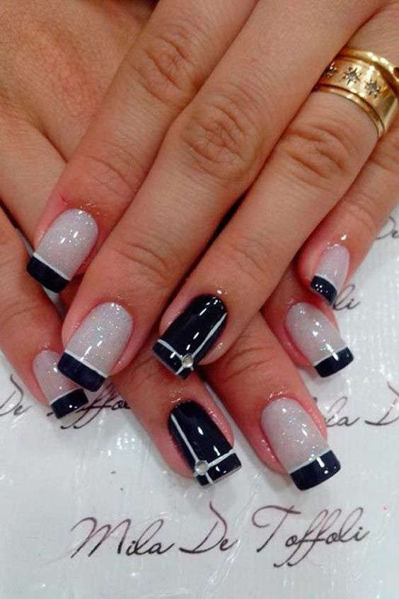 Flaunt your sun kissed nails with this white and midnight blue themed French manicure. The base color is coated in beige and tipped with midnight blue polish, lined with a pure white color. The other nails are coated in reverse, matte midnight blue with white streaks topped with a clear bead at the intersection.