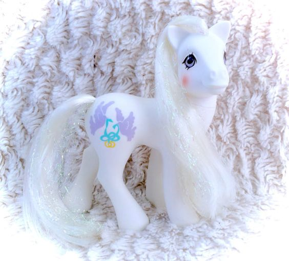 An absolutely stunning 1989 Bride My Little Pony! Her body is nearly flawless. The tinsel in her hair is a little crinkly, but still displays wonderfully!  Please see all pictures up close for a thorough representation of the item! I have TONS more cute vintage items like this one for sale in my Etsy shop - check it out for SUPER CHEAP combined shipping discounts. ;) I ship WORLDWIDE from a clean, pet & smoke-free home! Please note that shipping times will be slower OUTSIDE of the US…
