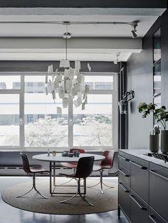 Sala de jantar com mesa redonda de mármore branca, tapete rústico e lustre lindo, de ingo maurer