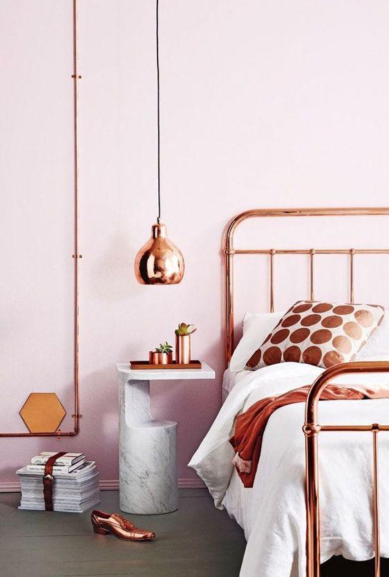 Cama e luminária de cobre, mesa de mármore no quarto com paredes rosa: