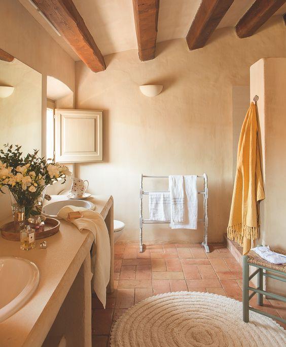 En el baño. Toallero de madera de Otranto y toallas de Calma House y Matèria. Alfombra y jarra de flores con plato, de India & Pacific.