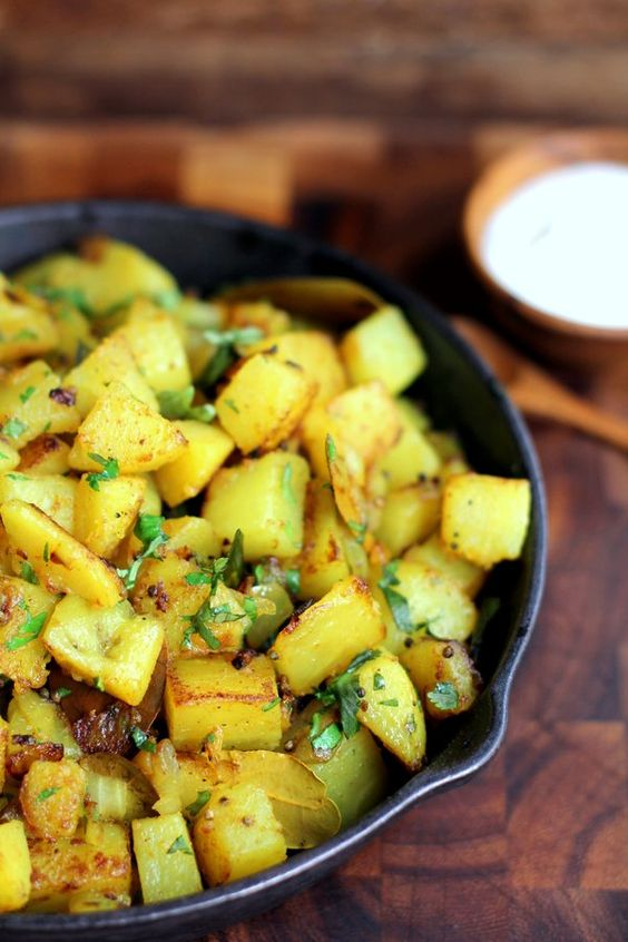 Aloo Bhaji 1 Tablespoon vegetable oil 1 teaspoon mustard seeds 6 dried curry leaves 2 green chilis, sliced into 4 pieces each 3 medium potatoes, boiled, peeled and cubed 1 large onion, finely chopped ¼ teaspoon turmeric powder juice from ¼ lime 2 tbsp fresh coriander leaves, chopped salt, to taste