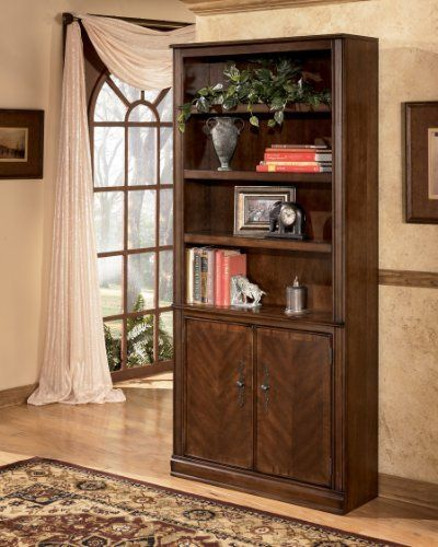 Medium Brown Large Door Bookcase Signature Design by Ashley Furniture by Ashley. Save 12 Off!. $502.01. With rich traditional style infused with a European flair, the sophisticated elegance of the Hamlyn home office collection is sure to enhance the beauty of any home office decor. The rich medium brown finish beautifully covers an exquisite cherry veneer that is enhanced with a sophisticated Prima Vera inlay veneer to create an overall traditionally styled design. With the rich look...