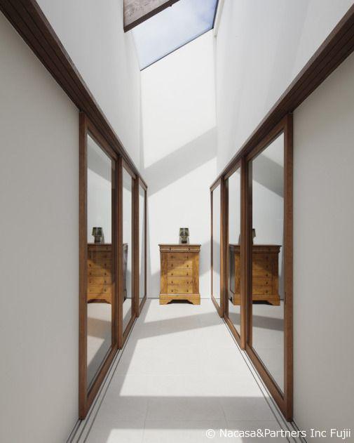 ガラス張りにした天井の開口から光が差し込む明るい廊下 内神の家